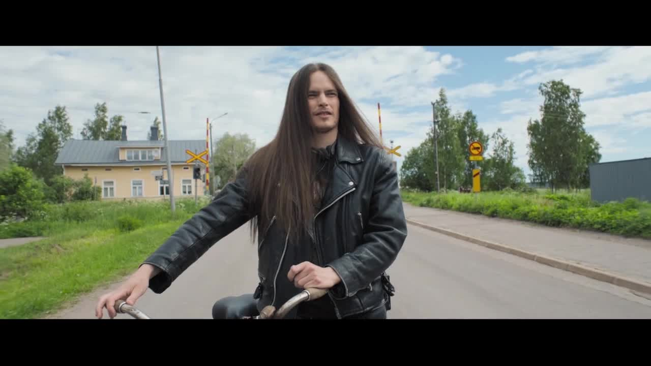 一长发男子推车走着,被几个修理工嘲笑,戴上耳机骑车离开