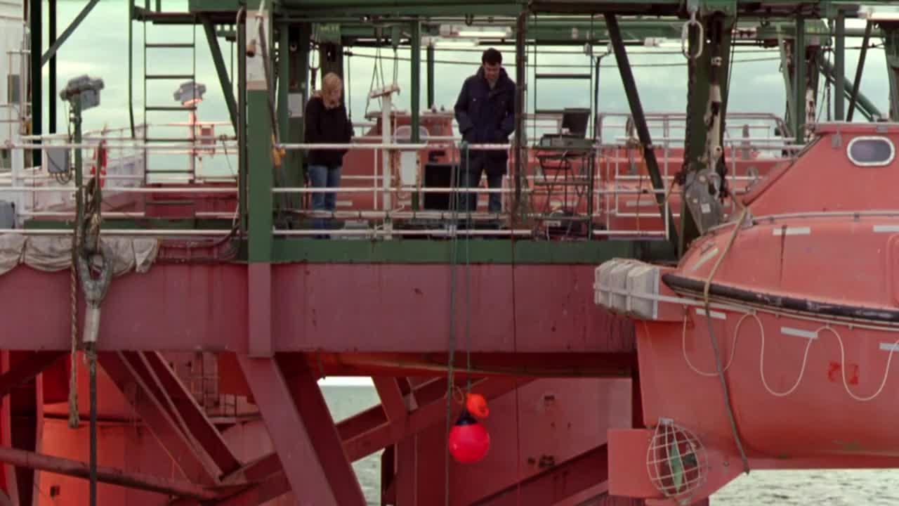 两人在船上聊天,男子给女子解释机器的用处,竟还拿起来给看