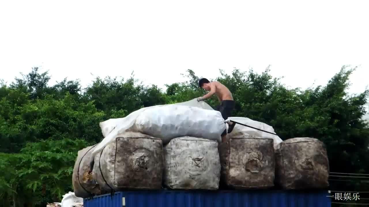 大雨来临,男子给货车满载的货物盖塑料薄膜,站得太高像表演杂技