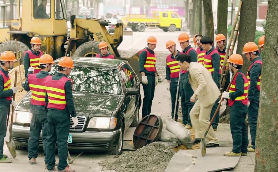 道路施工,男子还开着大奔横冲直撞,结果车轮陷入下水口了