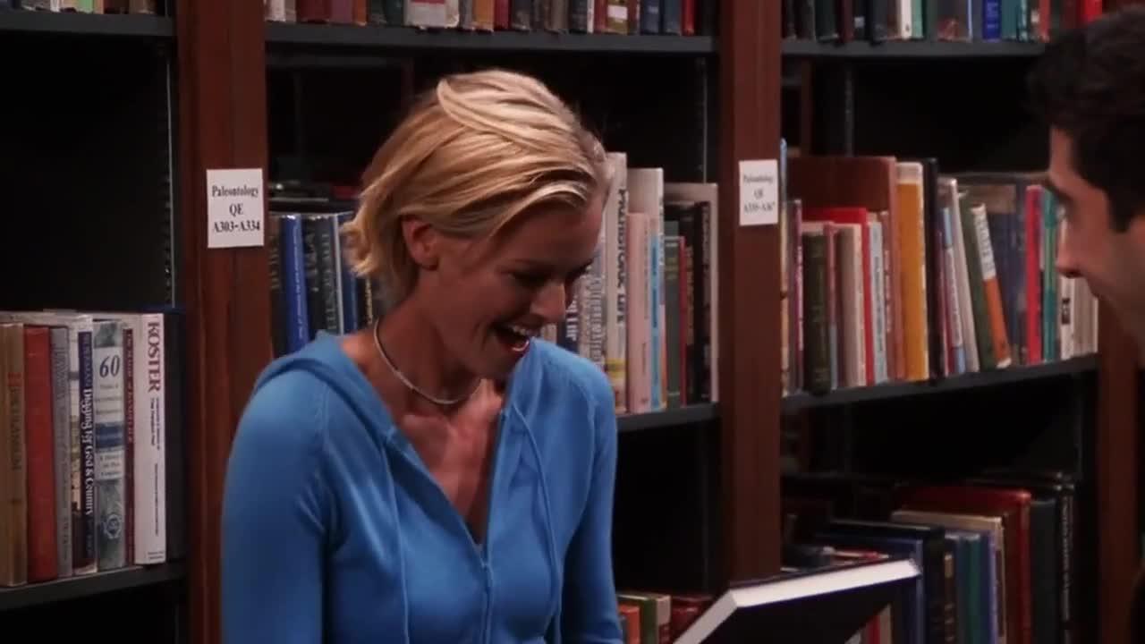 女孩拿着一本书很激动,表示很惊讶,因为作者就在旁边