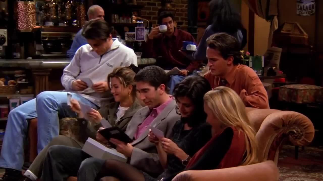 一群人坐在一起看照片,发现了好多好玩的瞬间,场面很欢乐